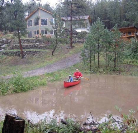 Mark and Lily go canoeing in their soaked neighborhood.
