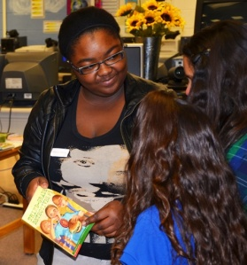 Ayana Bentley offers a book to students