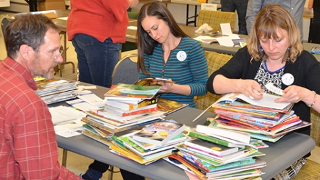 JCEA members Tony Tochtrop, Kimberly Douglas and Mandy Hayes place stickers and bookmarks in donated books.