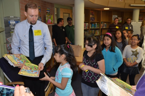 JCEA's Nate Golich passes out the books students get to take home